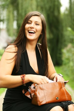 Happy smiling girl is rummaging in her brown handbag. she is very beautiful and has a lovely smile. she is sitting on a small bench.