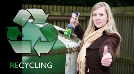 Girl is wasting , recycling a bottle in a glass container besides her home in her town district photo