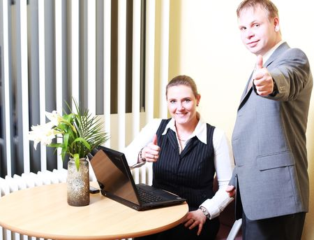 Sales Businesswoman and Business men makes profit and shows the thumbs up symbol. Thumb up in small office. photo