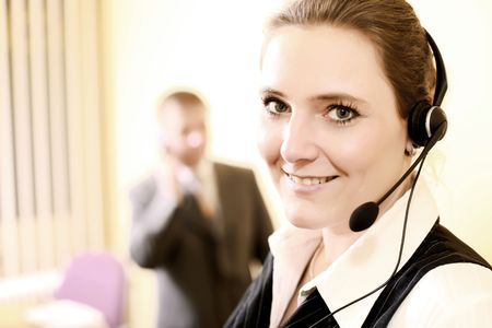 Sales agent and Business manager are on phone in the office. The Businesswoman is very attractive. She is wearing a headset and discuss friendly and smiling with customer.