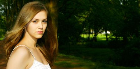 Cute young Teen Girl in a German park with dark background Stock Photo