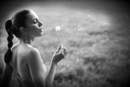 Attractive young woman is blowing into the blow ball. The pollen of the dandelion are flying away. Very healthy girl photo