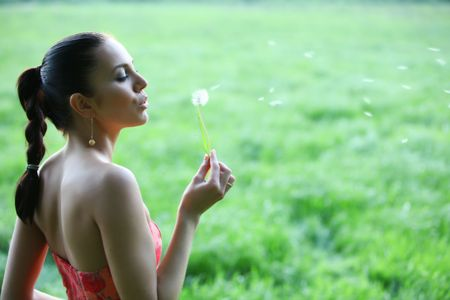 Attractive young woman is blowing into the blow ball. The pollen of the dandelion are flying away. Very healthy girl