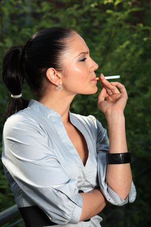 Business Woman Lady is smoking a cigarette and wachtes around