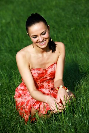A perfect dark haired woman, wearing a nice red summer dress, is sitting on a fresh green grass meadow and relaxing in the sun Stock Photo