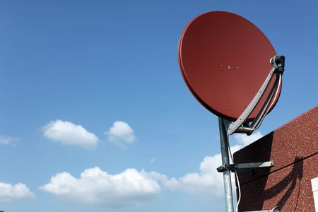 Satellite Dish on a garage with LNB. Blue Sky and white clouds in background, Fokus is right side view.
