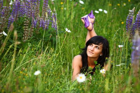 beautiful girl enjoys the summersun. she is laying down on the big fresh green meadow with the purple lavender flowers. it is summertime and pollen count