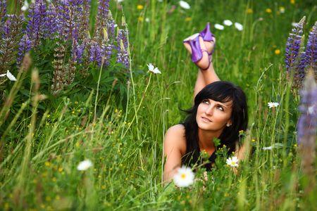 Schönes Mädchen genießt die summersun. sie ist mit auf die große frische grüne Wiese mit den lila lila Blumen. Es ist Sommer und Pollen Standard-Bild - 4935300