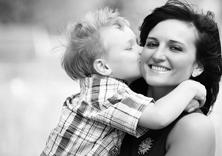 Mother Mum and her child son kissing and she is very happy. good relationship in this familiy is called motherly love.
