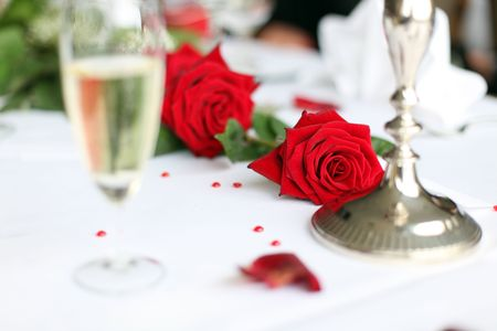 Photo shows a nice red rose on a wedding decorated table with a glass of sparkling wine and some small hearts photo