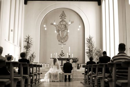 wedding ceremony black and white in church with benison mercy from god. Jesus picture like angle protect the bridal couple. photo made from behind.