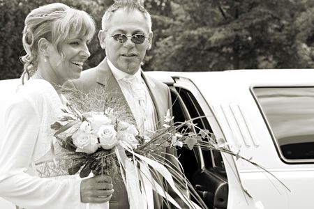 wedding couple is standing beside the limousine on the wedding day. black and white photo. groom with sunglass like Mafia Boss photo