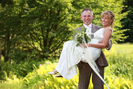 fresh married couple - he is carrying her wife bride bridal on his arms with cute white wedding dress
