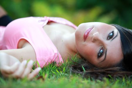 lays down: Busty young girl laying lays down on a meadow in grass
