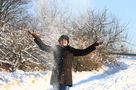 snowscene: Girl in snow is throwing white powder snow into the blue sky. She is wearing a nice hat. Stock Photo