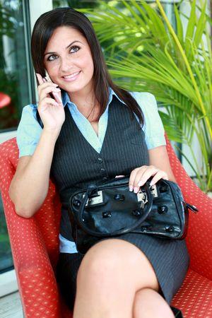 busty: Mooie Busty meisje is met een mobiel mobiele telefoon te bellen. Ze is het dragen van een jurk bedrijf en lachend met schone witte tanden.