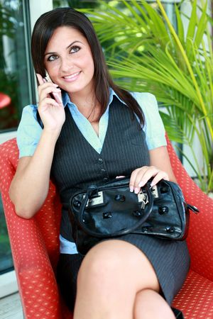 dark haired woman: Pretty Busty Girl is phoning with a mobile cellphone. She is wearing a business dress and smiling with clean white teeth.
