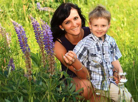 Mutter und Sohn auf einer großen grünen colorful grün Gras-Wiese. Frühling und Sommer Sonne.  Standard-Bild - 6700471