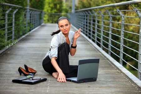 pigtailed smoking business lady with laptop relaxes her cigarette break and sitting on the outdoor summer ground photo