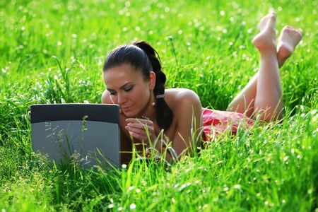 Girl with laptop use wireless internet connection and checking email on a summer spring meadow photo