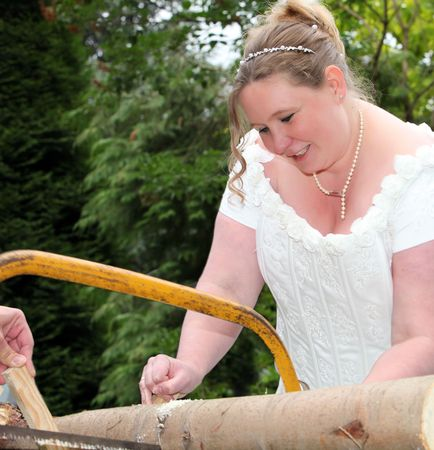 Bridal is sawing wood with a saw on her wedding day. The Marriage was in white and the bride pregnant.
