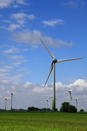 Wind Ernergie energy - turbine generator below nice blue cloudy sky. another group of windmills as alternative energy are in the background Stock Photo