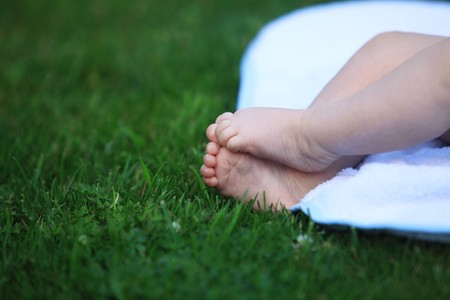 baby feet on meadow. infant feets on white towel and on green grass meadow Stock Photo