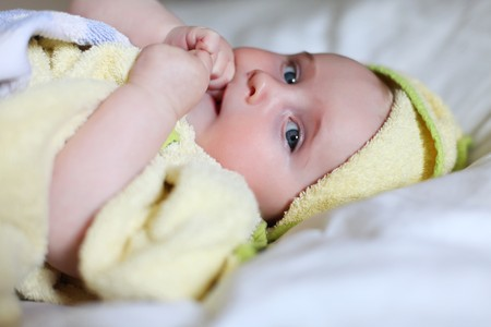 Cute Baby with blue eyes on a white bed with a yellow towel around her body after bathing. baby is very sweet and cute. she is sucking on her right hand at her small thumb.