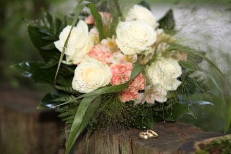 wedding bouquet with gold rings from groom and bride with the flowers on the wood. the flower is a yellow rose with some green. fresh roses. photo