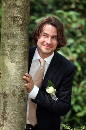 Young single groom is waiting and looking for his bride behind a tree photo