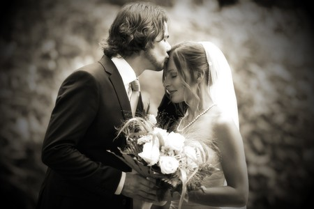 Bride and groom are tender kissing after the engagement. the marriage was on a sunny day. it was a young couple. photo was changed into black and white. kissing head Stock Photo