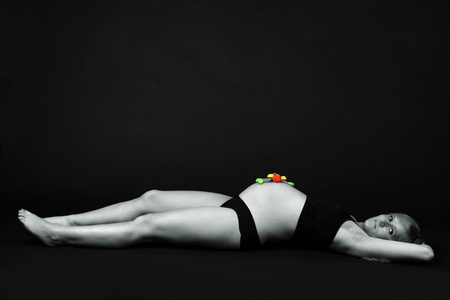 Pregnant woman is laying down on a black floor in front of a black background wall photo