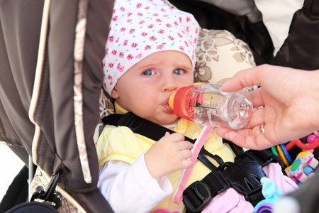 teats: Baby girl is drinking water while sitting in her buggy. Stock Photo