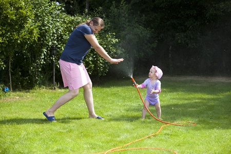 Child playing with garden hose and makes her mother wet . Real Fun photo