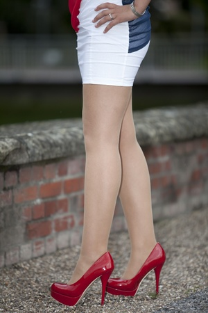 Red high heels - Woman with mini skirt standing there with her long legs and white nylons photo