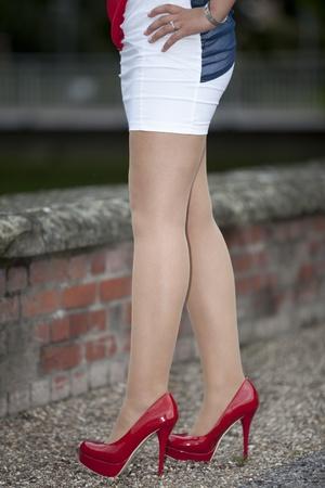 tacones negros: Red zapatos de tacón alto - Mujer con mini falda de pie con sus piernas largas y medias blancas