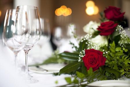 luz de velas: Decoración de la boda mesa se levantó - La foto muestra un bonito color rojo se levantó en una boda decorada mesa con una luz suave en el fondo y vasos vacíos. Fuera de foco se puede ver sparklne vasos de vino.