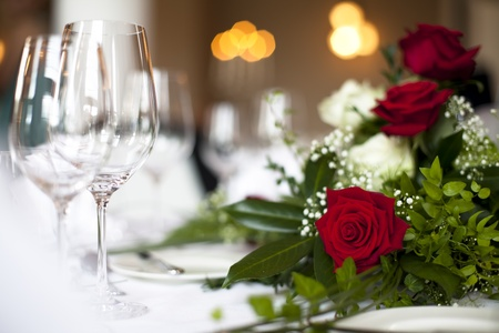 Svatební stůl dekorace růže - Fotografie ukazuje pěkný červená růže na vyzdobený stůl svatební s měkkým světlem v pozadí a prázdných sklenic. Vymáhání můžete vidět sparklne sklenice na víno. Reklamní fotografie