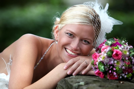BEAUTIFUL BRIDE WITH BOUQUET Beautiful blond bride holding bouquet of pink and white flowers is smiling and shows her white teeth
