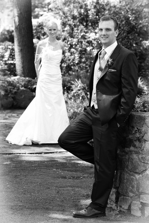 Bride defocussed, male in focus black and white photo of a sunny white wedding day photo