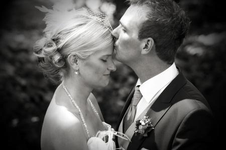 arracher: Mariage tr�s romentic baiser dans un parc avec une jeune mari�e blanche et une messieurs aux cheveux noirs comme bridgegroom. baiser sur le front de noces