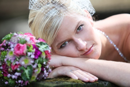 fair skinned: BEAUTIFUL BRIDE WITH BOUQUET Beautiful blond bride holding bouquet of pink and white flowers is smiling and shows her white teeth