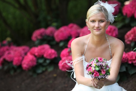 BEAUTIFUL BRIDE WITH BOUQUET Beautiful blond bride holding bouquet of pink and white flowers is smiling and shows her white teeth Stock Photo - 11864995