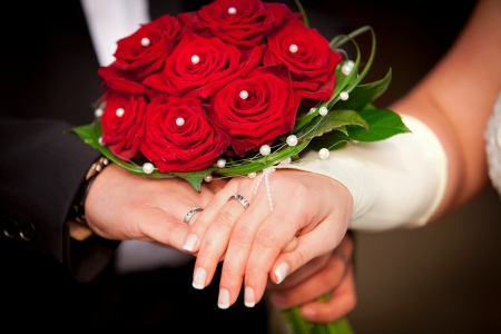 bridal bouquet: Red wedding roses with pearls  Hands with rings of bridal and bridgegroom with red roses and pearls and also some kind of gloves Stock Photo