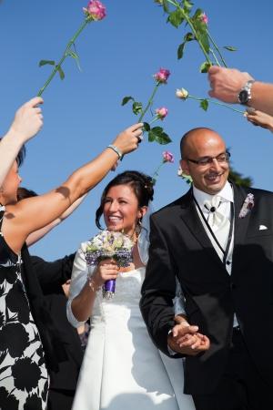 pareja de reci�n casados ??se est� riendo y caminando a trav�s de un t�nel de las rosas photo