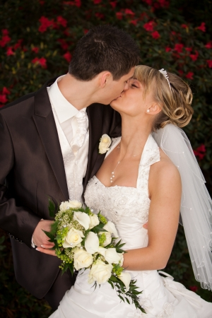 Young couple just married  groom kiss his pretty bride after the wedding ceremony  she is blond and wearing a nice diadem  background red roses and foreground yellow bouquet roses photo