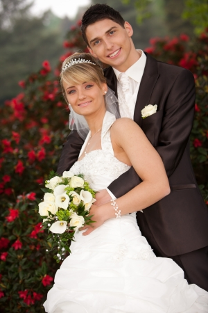 Bride leaning against groom  Young couple just married  groom and pretty bride are looking into the camera to the photograph other after the wedding ceremony  she is blond and wearing a nice diadem  background red roses and foreground yellow bouquet roses photo