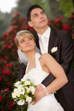 Bride leaning against groom  Young couple just married  groom and pretty bride are looking into the camera to the photograph other after the wedding ceremony  she is blond and wearing a nice diadem  background red roses and looking against the sky  photo
