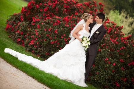 Jong paar net getrouwd bruidegom wil zijn mooie bruid te kussen na de huwelijksceremonie ze is blond en het dragen van een mooie diadeem achtergrond rode rozen en voorgrond geel boeket rozen