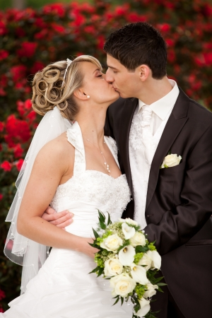 feleségül: Fiatal pár ifjú vőlegény megcsókolja a szép menyasszony az esküvő után szertartás ő szőke, és rajta egy szép diadém háttér piros rózsák és előtérbe sárga csokor rózsát
